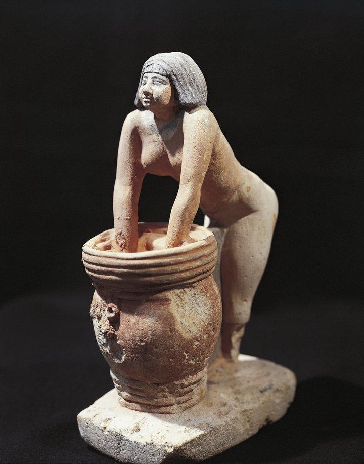 Alrededor 1900: una estatuilla de piedra caliza pintada de una mujer que hace cerveza en Egipto.